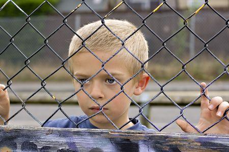 Un portrait d'un jeune garçon regardant à travers une clôture à mailles losangées