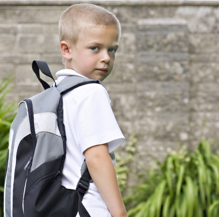 Young boy wearing a backpack ready for school Stock Photo