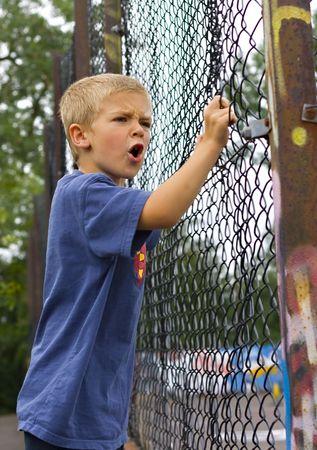 delincuencia: Un muchacho joven enojado gritando a trav�s de un cerco