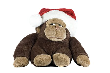 A toy gorilla wearing a santa hat isolated on white