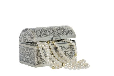 Simulated pearl beads spilling out of a tooled silver casket Stock Photo