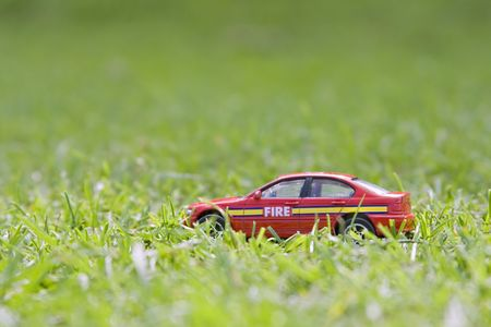 discarded: A childs small red fire car discarded in the grass