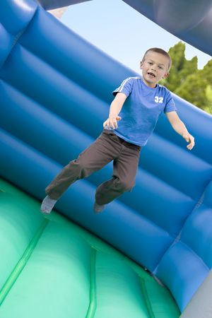 6 year old: Portrait of a cute six year old boy jumping on a bouncy castle moonwalk