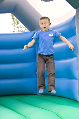 Portrait of a cute six year old boy jumping on a bouncy castle moonwalk