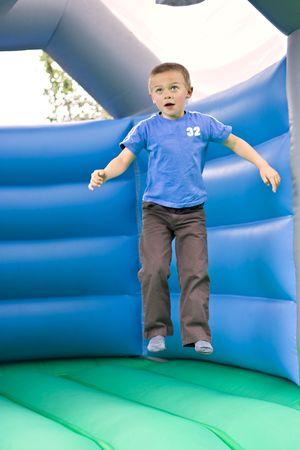ni�o saltando: Retrato de un ni�o de seis a�o de edad lindo saltando sobre un moonwalk castillo saltarinas
