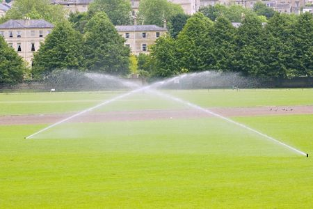 Two sprinklers irrigating a sports field in summer