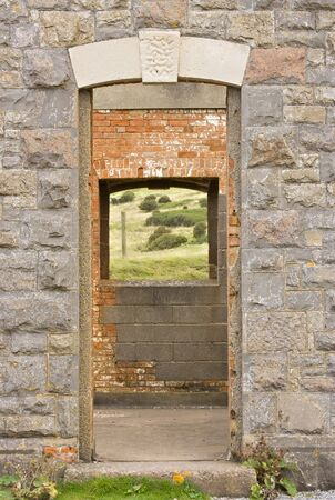 within: Open frame doorway looking out onto grassland