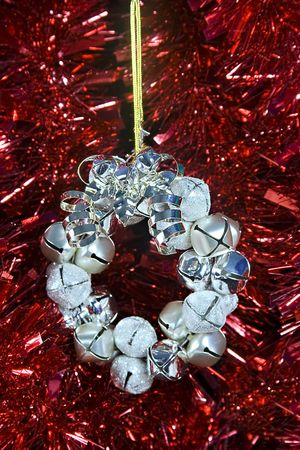 silver bells: A Christmas decoration with silver bells laying against some red tinsel