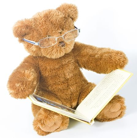 A wise old teddy bear looking at a book with the aid of his reading glasses Stock Photo