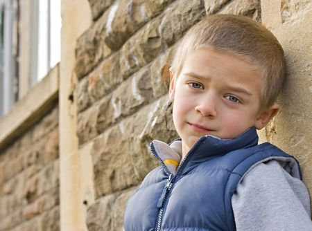 A portrait of a serious looking young boy leaning against a wall