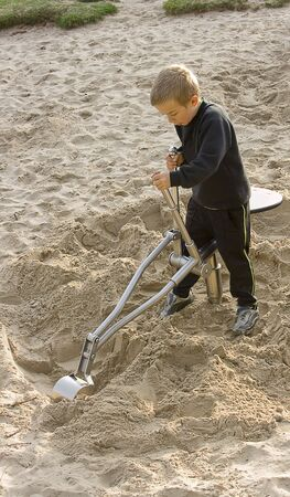 Ein Junge spielt auf einem Spielzeug Bagger in den Sandkasten im park Stockfoto - 6610214