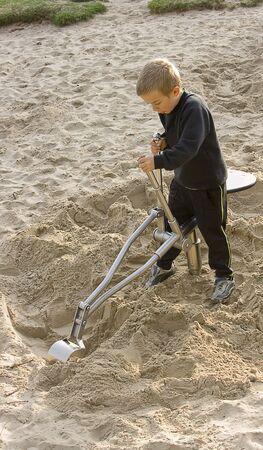 Ein Junge spielt auf einem Spielzeug Bagger in den Sandkasten im park Lizenzfreie Bilder - 6610214