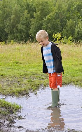 A young boy jumping in a muddy puddle wearing his wellington boots Standard-Bild