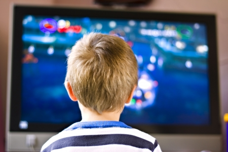 screen tv: Candid close up portrait of a cute six year old boy watching television