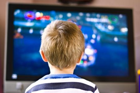 personas mirando: Cierre franco hasta el retrato de un niño de seis años cute viendo la televisión