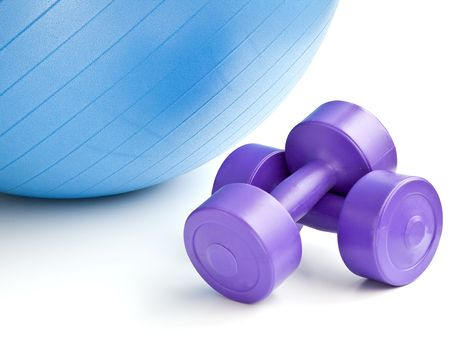 fitness equipment: A blue fitness ball and a pair of dumbells Stock Photo