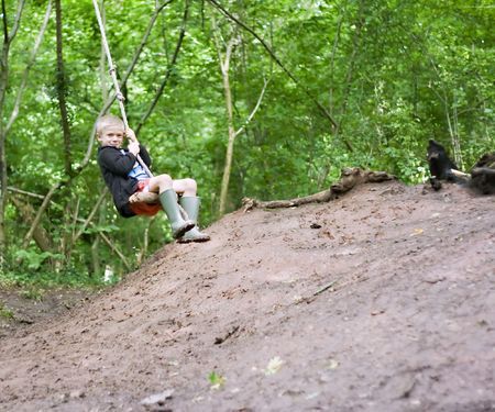 Young boy swinging on a rope swing in the woods Standard-Bild