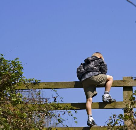 young six year old boy climbs over a gate Stock Photo