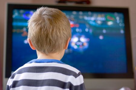 Candid close up portrait of a cute six year old boy watching television photo