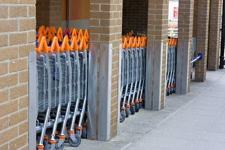 A row of shopping trolleys lined up outside a supermarket photo
