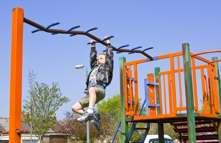 Young six year old boy plays on the equipment in a children's playpark Standard-Bild