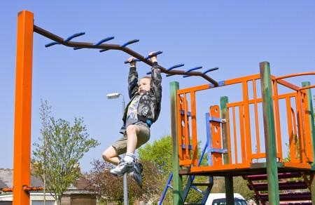 Sechs Jahre alter Junge spielt auf die Ausrüstung in ein Kinder Spielpark Standard-Bild - 6959416