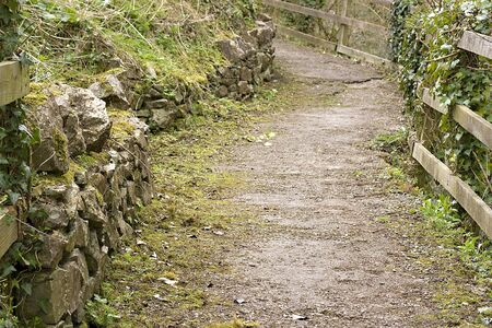 Winding rural path curving uphill around a bend photo