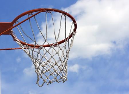 An orange basketball hoop against a blue sky