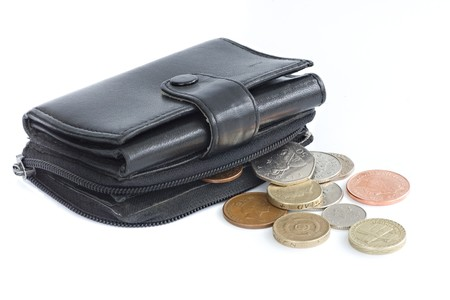 A black purse holding UK sterling coins Stock Photo
