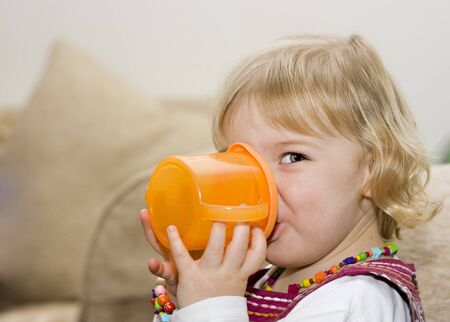 An adorable cute little girl drinking from a training cup photo