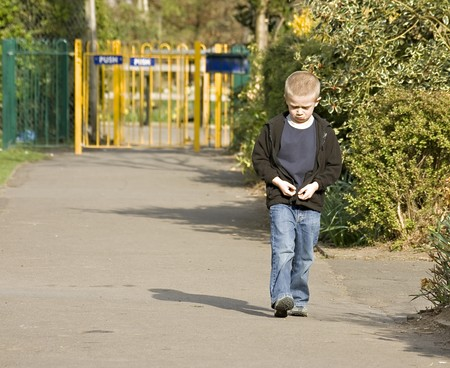 A sad or angry six year old boy waliking through the park Standard-Bild