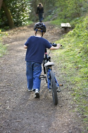 A young six year old boy pushing his bike through the woods photo