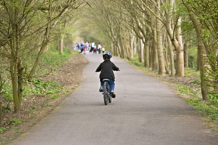 A young six year old boy riding his bke along a cycle trail photo