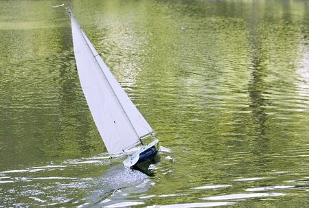 A radio control toy yacht sailing on a lake photo