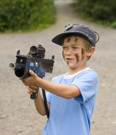 Ein kleiner Junge mit Camouflage Farbe auf seinem Gesicht, das Vorbereiten der Krieg Spiele spielen Standard-Bild - 7653077