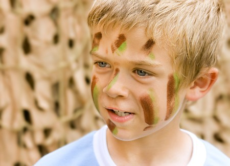 A young boy with camouflage paint on his face Standard-Bild