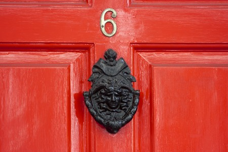 A red wooden door with a large Georgian door knocker Stock Photo