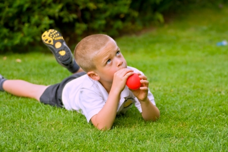 Young six year old boy holding a red balloon