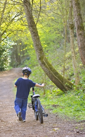 A young six year old boy pushing his bike through the woods