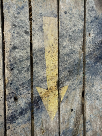 yellow down arrow on the old vertical wood texture