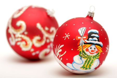 Two red christmas balls with drawing of snowman  and snow isolated on white background photo