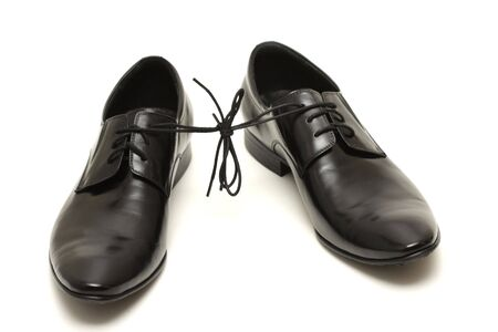 Pair of black man shoes tied together isolated on white background