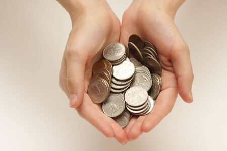 Silver coins in hands on abstract background photo