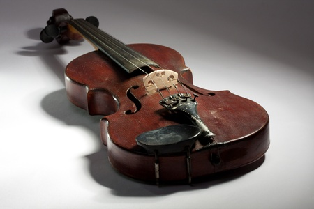 extremely old scratched violin on light background photo