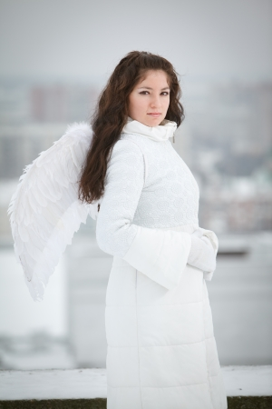 Woman with angel wings standing and looking at camera photo