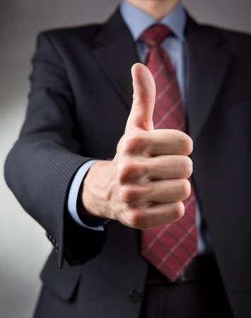 thumbs up symbol: Businessman showing thumbs up sign  Neutral background