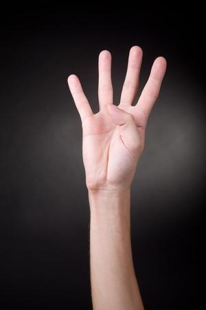 pantomima: El número cuatro Mano humana que muestra cuatro dedos Foto de archivo
