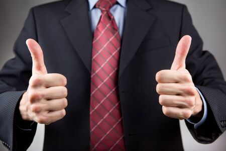 Businessman with two thumbs up  Neutral background photo