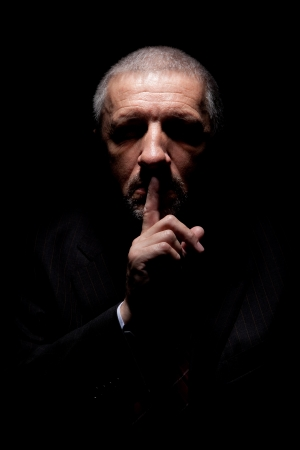 Scary mature man gesturing silence  Black background