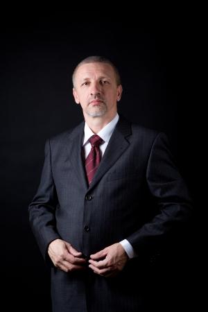 그의 검은 양복에 손을 잡고 성숙한 잘 생긴 사업가